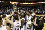 Kansas forward Mario Little takes a look at the Las Vegas Invitational trophy with his teammates following the Jayhawks' 87-79 win over Arizona, Saturday, Nov. 27, at the Orleans Arena.