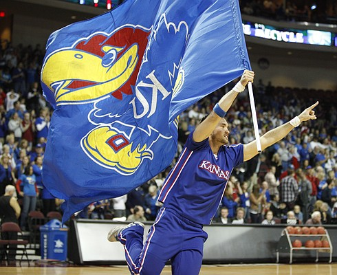 A yell leader runs a KU flag around the court prior to tipoff against Arizona.