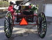 Kay Wolfe climbs into an Amish road cart to take a test ride before the 2010 Old-Fashioned Christmas Parade in downtown Lawrence. The 2010 event is on Dec. 4.