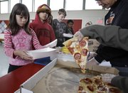 Fairmeadow Elementary School fourth-grade student Juliet Lee, left, orders pepperoni pizza during a school lunch program Thursday in Palo Alto, Calif. More children would eat lunches and dinners at school under legislation passed Thursday by the House and sent to the president, part of first lady Michelle Obama's campaign to end childhood hunger and fight childhood obesity.