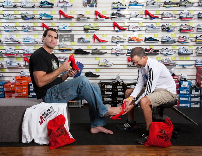 Former Kansas University basketball standout Scot Pollard tries on a red stiletto with the help of Steve Sell, an employee at Garry Gribble's Running Sports in downtown Lawrence. They are featured on the cover of the 2011 Red Shoe calendar, which raised money for The Willow Domestic Violence Center in Lawrence.