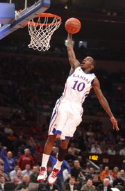 Kansas guard Tyshawn Taylor soars in for a dunk on a breakaway against Memphis during the first half of the Jimmy V Classic at Madison Square Garden in New York on Tuesday, Dec. 7, 2010.