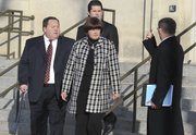 Former University of Kansas athletic department consultant, Thomas Ray Blubaugh, and his wife Charlette Blubaugh, left and center, leave the U.S. Federal Courthouse, in Wichita, Kan., on Wednesday, Dec. 8, 2010, after being arraigned on a charge of conspiring to commit wire fraud. Prosecutors say the couple, along with others, are charged with stealing athletic tickets and scalping them for cash to ticket brokers and third parties outside the university totally $5 million.