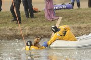 Lawrence firefighter Alex Thomas, left, helps firefighter James Barkley rescue a dog from a pond on East 1100 Road on Thursday, Dec. 9, 2010.