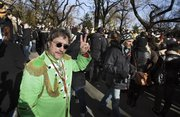 Raymond Brisson, left, of Cranston, R.I., dressed as John Lennon, flashes a peace sign Wednesday as he joins the crowd at the Imagine mosaic in the Strawberry Fields section of New York's Central Park on the 30th anniversary of Lennon's death.
