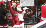 Paige Donnelly and her mother, Patty Donnelly, wave as a mass of Santas walk through downtown Lawrence on Saturday.