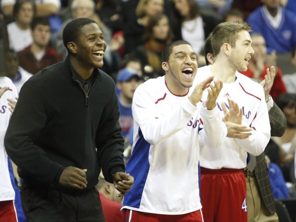 Kansas players Josh Selby, left, Niko Roberts, and Jordan Juenemann celebrate a dunk by teammate Markieff Morris during the second half, Saturday, Dec. 11, 2010 at the Sprint Center in Kansas City.