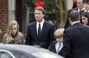 John Edwards and his children, Emma Claire, left, Jack and Cate, far right, leave the funeral service for Elizabeth Edwards on Saturday at Edenton Street United Methodist Church in Raleigh, N.C.
