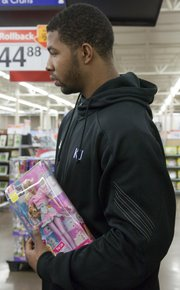 Markieff Morris holds a Barbie doll while shopping for the llittle girl on his list. The KU men's basketball players made their annual shopping trip to Walmart to give back to the community.