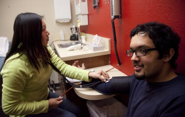 Lawrence resident Ansib Chaudhry has his vitals taken by Health Care Access volunteer Nan Wang before being checked out by a doctor for some potentially fractured facial bones Tuesday, Dec. 14, 2010, at Health Care Access, 330 Maine. The clinic provides medical care for low-income, uninsured Douglas County residents.
