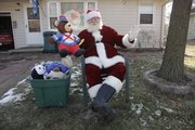 Lawrence resident Chris Hartman sits in front of his home on West Ninth Street handing out toys to children passing after school. Hartman has been dressing up as Santa Claus for about 30 years.