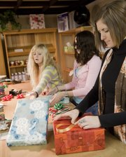 Wrapping gifts gets easier and easier with repetition, and the courtesy wrappers at Weaver's Department Store have it down to an art. From left Wednesday were Lisa Hilmes, Paula Kyriakos and Megan Ballock.
