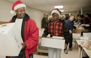 J.R. Demby, left, and his daughter Rianon Wallace-Demby pick up 18 Christmas meals to deliver to North Lawrence residents. The two were picking the meals up during the Lawrence Community Christmas dinner at First United Methodist Church.