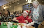 Bob Taylor, Mary Louise Taylor and Grace Oshel visit over the Christmas dinner at First United Methodist Church on Saturday.