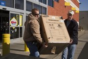 Nick Rausten, left, and Mike Bergman, both of Lawrence, load a newly purchased dishwasher into the bed of Rausten's truck Sunday afternoon at Best Buy. Many shoppers braved the cold weather in search of specials and bargains as stores around Lawrence opened for business the day after Christmas.