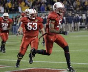 North Carolina State wide receiver Jarvis Williams (5) celebrates his 7-yard  touchdown catch with center Camden Wentz (53). N.C. State defeated West Virginia, 23,-7, in the Champs Sports Bowl on Tuesday in Orlando, Fla.