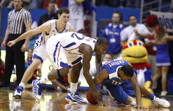 Kansas guard Josh Selby gets tied up with UT Arlington guard Cameron Catlett during the second half, Wednesday, Dec. 29, 2010 at Allen Fieldhouse. In back is Kansas guard Tyrel Reed.