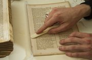 Hagen Miller uses a bone folder tool to prepare pages from an 1854 family Bible.