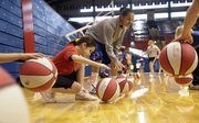KU point guard Angel Goodrich, center, shows the art of dribbling to Maria Matamoros, 8, of Lawrence, on Saturday, Jan. 1, 2011, at the women&#39;s basketball team&#39;s Holiday Hoops Clinic at Allen Fieldhouse.