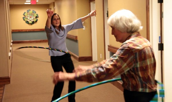 WellCommons editor Karrey Britt gets hula-hoop lessons from Virginia Acheson, 85, right, in 2011.