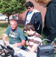 Basehor-Linwood High School freshmen Nathan Lucas, sitting, Jacob Zamora, standing at left, and Spencer Brown, right, seek out other radio operators, helped by sponsor Bob Kimbrell, during the School Club Roundup event in October.