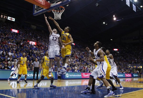 Kansas guard Brady Morningstar squeezes a bucket past UMKC forward Trinity Hall during the second half on Wednesday, Jan. 5, 2011 at Allen Fieldhouse.