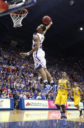 Kansas guard Travis Releford soars in for a windmill dunk in front of UMKC defenders Tr