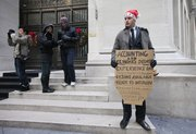 Jesse Paloger holds up a sign while standing on Wall Street as he hopes to find a job in New York in this Dec. 15, 2010, photo.