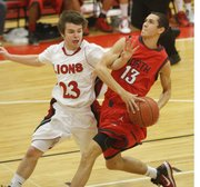 Lawrence High junior Shane Willoughby, left, tries to reach for a steal against Olathe North's Zach Downing on Friday night. Olathe North defeated LHS, 58-38.