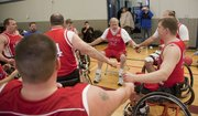 Wheelhawks coach and player Ray Petty, Lawrence, center, instructs the team during a timeout.