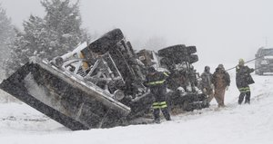 Crews work to overturn a Douglas County snowplow Monday that  flipped over on U.S. Highway 56 about four miles west of U.S. Highway 59. Snow-packed roads throughout the county made for difficult driving conditions early Monday.