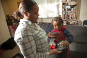 Rachelle Esperance, Lawrence, will always remember surviving the Haiti earthquake along with her 3-year-old son, Olivier. On the one-year anniversary of the earthquake, Jan. 12, 2011, the two look at a photograph of Esperance's father and Olivier's grandfather, Gerard Esperance, who lives in Haiti. The picture was taken when Gerard was in Lawrence for a visit in June.