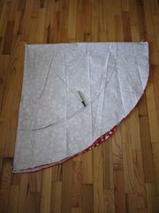 Fold the circular tablecloth into quarters. Use binder clips to keep it from shifting. Katie used these rather than pins so she wouldn't make holes in the fabric. Clip the string to the center point of the tablecloth, the corner of the folds (at upper left in photo). With a marker or chalk, use the string as a compass to mark the size of the tabletop. Keep even tension on the string as you pull it across the tablecloth. Cut all layers along this line. You'll end up with a smaller circle.