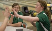Free State bowler Michelle Schieffer, left, high-fives teammate Sarah Perala, right, after Perala bowled a strike during their meet Thursday, Jan. 13, 2011, at Royal Crest Lanes.