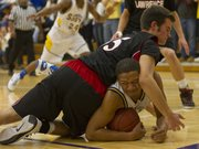 Olathe South junior forward Kameron Lindsay, bottom, beats Lawrence High senior Garrett Wagner to a loose ball during Friday night's game in Olathe.