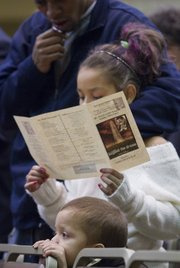 """Rejjin Jackson, 9, and her father, Ronnell Jackson, follow a song sheet together while 6-year-old Davonte Mator peers over the seats Monday night during a celebration of Martin Luther King Jr. at the Kansas Union. This year's theme was """"Beyond the Dream: Now What?"""""""