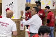 President Barack Obama paints colorful cartoon apples in a student lunchroom at the Stuart Hobson Middle School in Washington as he observes the Martin Luther King Jr. holiday by participating in a community service project on Monday. Martin Luther King Jr. was assassinated in 1968 in Memphis, Tenn.