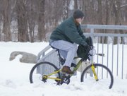 Lawrence resident Terry Culp maneuvers his bike through snow Friday on his daily commute to work.