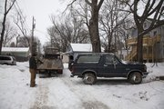 Tow crews begin to load a late-model Ford Bronco after the body of a  58-year-old Lawrence woman was found inside Saturday morning parked behind a house in the 800 block of Tennessee Street.