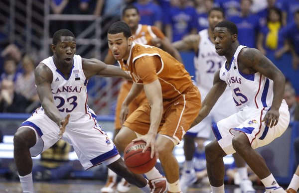 Kansas defenders Mario Little, left, and Elijah Johnson look to trap Texas guard Cory Joseph during the first half on Saturday, Jan. 22, 2011 at Allen Fieldhouse.