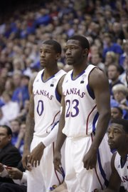 KU's Thomas Robinson (0) and Mario Little watch the end of the Jayhawks' loss to Texas on Saturday at Allen Fieldhouse. Robinson will not be with the team in Colorado.
