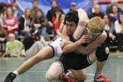 Lawrence High's Andrew McLees works against Free State's Austin Magdaleno in the 130-pound class on Wednesday, January 26, 2011 at FSHS.