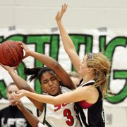 Free State's Abbey Casady (right) defends Highland Park's Shanise Brooks Thursday, Jan. 27, 2011 in the first round of the Firebird Winter Classic at FSHS.
