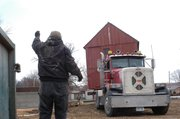 John Earnshaw guides a truck while moving the Shawnee Town barn in December. The barn is a fraction of the size of many structures he's moved over the years.