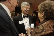 Gary Toebben, center, current president and CEO of the Los Angeles Chamber of Commerce and former president of the Lawrence Chamber of Commerce, is welcomed by Sherry, left, and Carol Schaub, of Lawrence, at the Holiday Inn Lawrence on Friday for the annual Chamber of Commerce meeting.