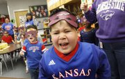 "Kennedy School student Mikey Gregorio belts out the lyrics to ""I&squot;m a Jayhawk"" as he and other students in Jill Anderson&squot;s class make their rounds performing Kansas University and Kansas State University songs and chants for other classes Friday, Jan. 28, 2011."