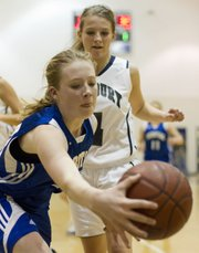 Veritas junior Ellen Phillips saves the ball from going out of bounds as Bishop Seabury senior Angela Thomas defends during Bishop Seabury's game against Veritas Christian School on Friday, Jan. 28, 2011 in Lawrence.