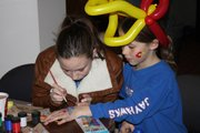 Kim Scherman, Kansas University junior and member of KU Environs, paints the hand of Josie Boyle, 8, Baldwin City, at the Take Charge Challenge kick-off party Saturday evening at Liberty Hall. The kick-off was also a watch party for the KU vs. K-State basketball team, and Boyle was having the name and number of her favorite KU player, Tyshawn Taylor, painted on her hand.