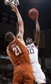 Texas A&M's David Loubeau (10) shoots over Texas defender Matt Hill (21) during the first half. The Longhorns won, 69-49, Monday in College Station, Texas.