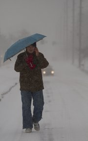 Yu Yang, a KU student from China, walks down 19th Street in blowing snow Tuesday. Yang was on his way to meet a friend after KU canceled classes Tuesday.